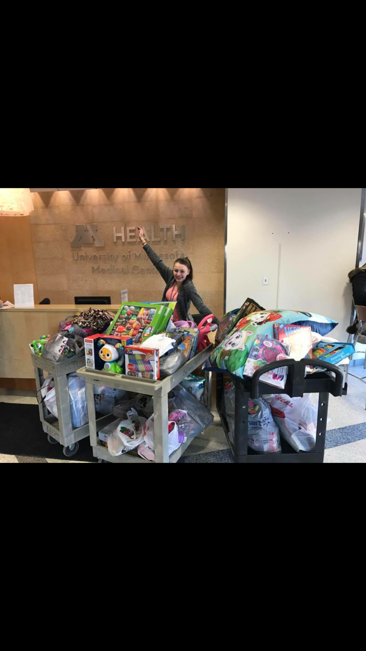 Gabby sitting next to a pile of gifts delivered to children in 2016